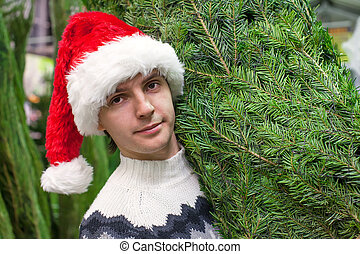 Close-up Young man buying a Christmas tree in the store