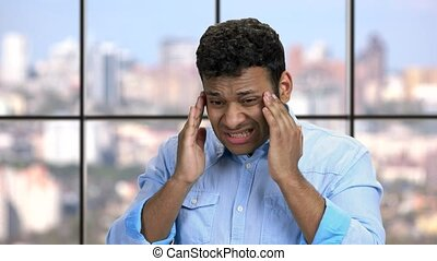 Close up young man suffering from migraine. Overworked businessman suffers from headache on windows background.