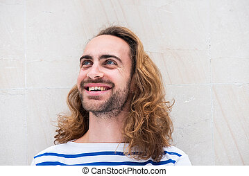 Close up young man with beard and long hair smiling and looking away against white background