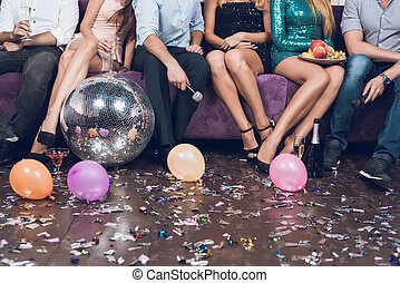 Close up. Young people rest in pairs in a nightclub. They are sitting on a large lilac sofa.