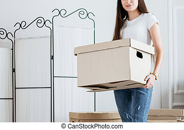 young woman carrying boxes in her new apartment