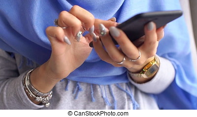 Close-up Young woman dials message on mobile phone. Slow motion.
