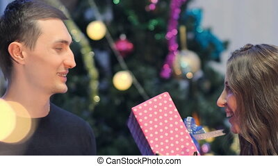 Close-up young woman gives gift to her boyfriend
