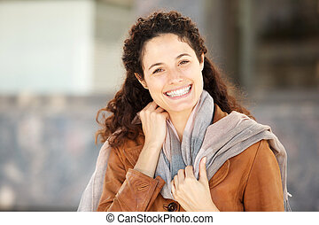 Close up young woman in coat and scarf smiling