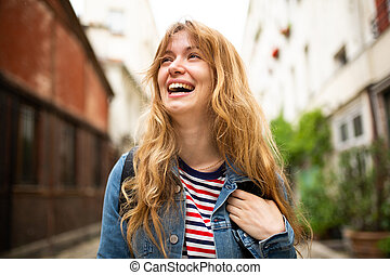 Close up young woman laughing outside in city