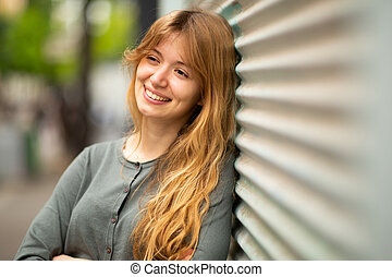 Close up young woman leaning against wall and smiling