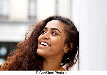 Close up young woman leaning against white wall and smiling