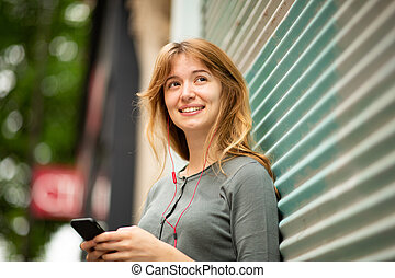 Close up young woman listening to music with earphones and cellphone outside