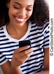 Close up young woman smiling and looking at mobile phone