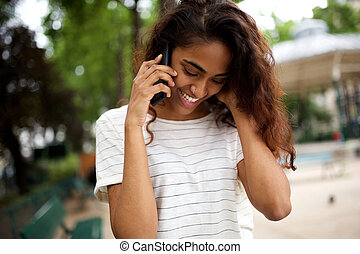 Close up young woman smiling and talking with mobile phone outdoors