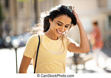 Close up young woman smiling with hand in hair outside