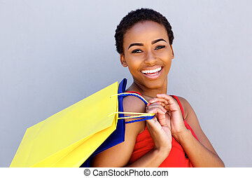 Close up young woman smiling with shopping bags