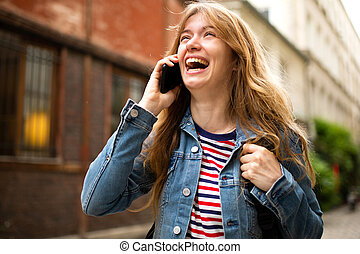 Close up young woman talking with mobile phone and laughing