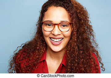 Close up young woman with glasses and curly hair smiling against blue background