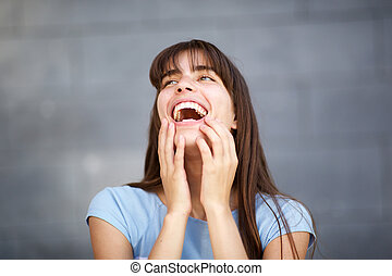 Close up young woman with long hair laughing against gray background