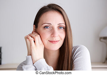 Close up young woman with long hair smiling and staring