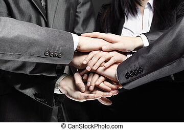 close up.a group of business people folded their hands together