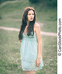 thoughtful young woman with long hair standing in a meadow