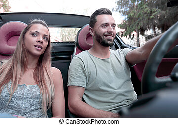 close up.beautiful couple sitting in the front seat of a convertible