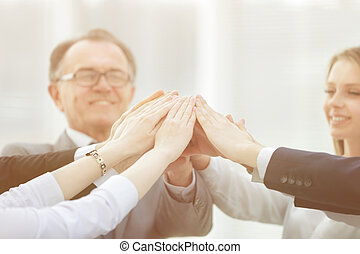 Business people raising their arms during meeting in office
