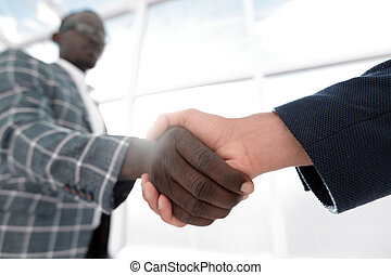 business people shaking hands in a bright office.