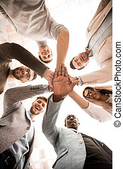 close up.business team standing in a circle and folded their hands together.