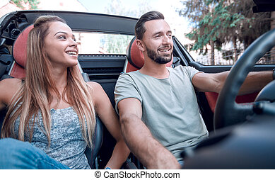 close up.happy couple sitting in the front seat of a convertible