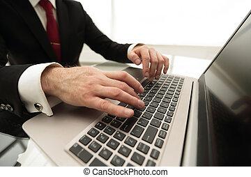 close up.modern businessman typing on a laptop.