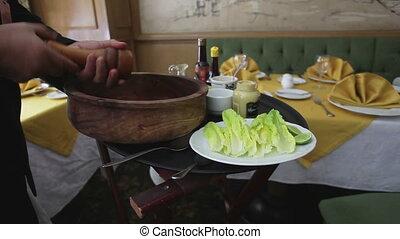 close-ups of a chef preparing a caesar salad in a restaurant