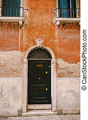 Close-ups of building facades in Venice, Italy. A wooden black door in an arched doorway with a metal grille on top, in the facade of a brick orange building in the Venetian style.