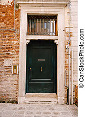 Close-ups of building facades in Venice, Italy. A wooden green front door in a stone doorway. The texture of a brick wall with communication pipes. An old intercom and a mailbox in the door.