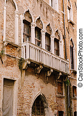Close-ups of building facades in Venice, Italy. An ancient balcony with stone arches and classic Venetian windows on the facade of a brick building.
