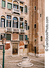 Close-ups of building facades in Venice, Italy. An old street well in the square in front of a brick house. There are many Venetian-style windows on facade of building. Vintage street lamp is green.