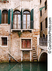 Close-ups of building facades in Venice, Italy. Beautiful Venetian windows with open wooden green shutters. An old red brick house next to a bridge over a small narrow canal.