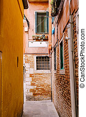 Close-ups of building facades in Venice, Italy. Cozy Venetian streets. Narrow street, between two houses. The first floor is a bare red brick, the second floor is a pink painted wall.