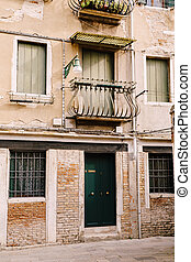 Close-ups of building facades in Venice, Italy. Green wooden door at bottom of brick house. Balcony with a forged fence. An old street lamp on the wall of an apartment building.