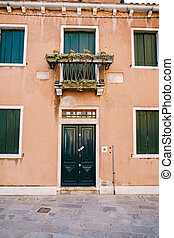 Close-ups of building facades in Venice, Italy. Two-storey peach-colored building with green wooden shutters for windows and door. A balcony above the front door with a forged metal grille
