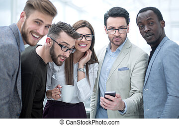 smiling business team looking at the smartphone screen