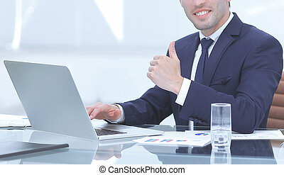 close up.smiling businessman working on laptop and showing thumb up