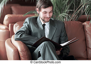 close up.smiling handsome businessman reading documents