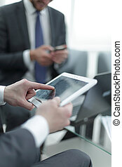 close up.the businessman uses a digital tablet in the workplace