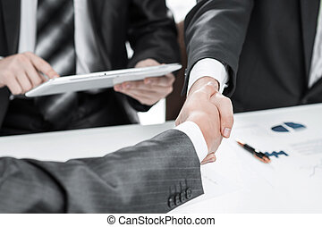 close up.the financial partners shaking hands over a Desk