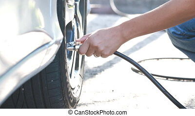 inflating car tire - close up,woman checking pressure and...