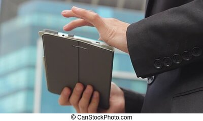 Close video of palms of man using tablet for work or...