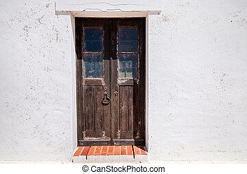 Close view of an old wooden door from a white house.