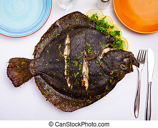 Close view of baked flounder on plate with parsley and lemon