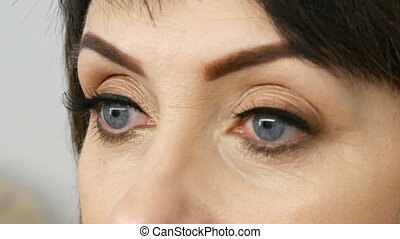 Close view of blue eyes with arrows and long false eyelashes...