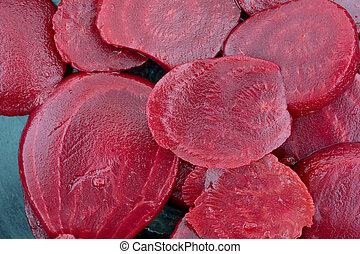 Close view of canned sliced beets in a cast iron skillet.