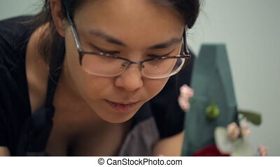 Close view of florist making flower composition inside office