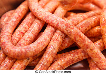 Close view of homemade raw thin sausages, meat production